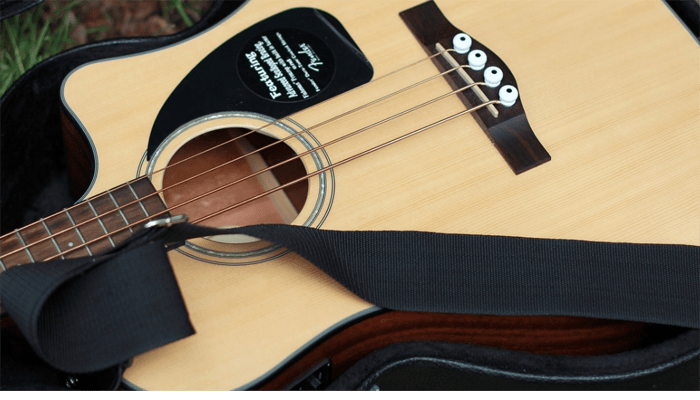 Acoustic guitar on the ground with strap